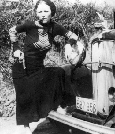 Bonnie Parker, posing with gun on hip and cigar in mouth